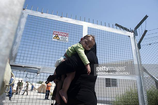 A refugee woman fleeing the war in Syria holds her child as she arrives at the Kokkinotrimithia refugee camp West of Nicosia in Cyprus on September 6...