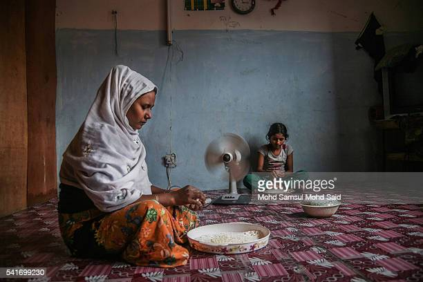 A refugee woman from the Rohingya ethnic minority works inside their house on June 20 2016 in Klang Malaysia According to the Office of the United...