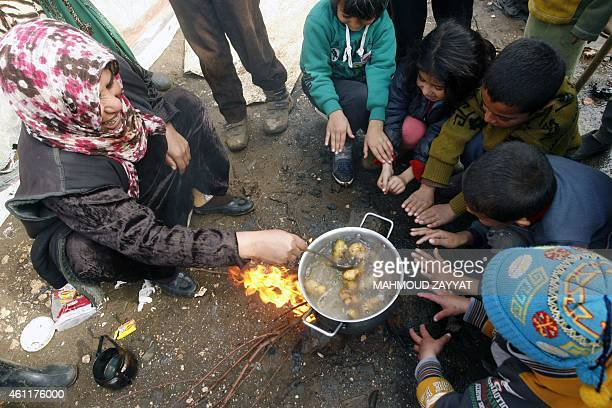 A refugee woman who fled the Syrian city of Raqqa cooks as children warm up around the fire at a camp housing families fleeing their war torn country...