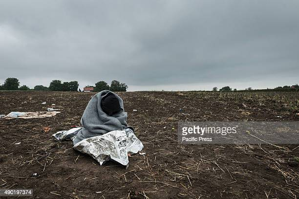 A refugee wraps himself while waiting to cross the SerbianCroatian border at the refugee camp of Bapska Millions of refugees flee from their...