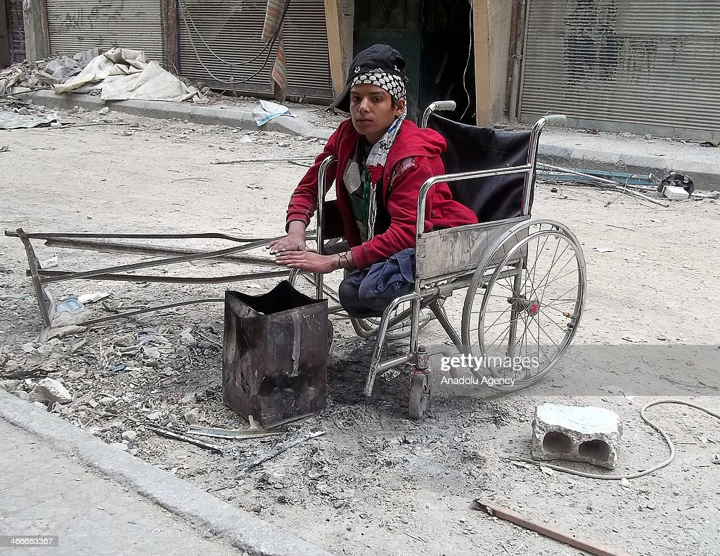 A refugee youth on a wheelchair warms himself with a fire in a steel canister at the Yarmouk Refugee Camp, in southern Damascus, Syria, on February 2, 2014.