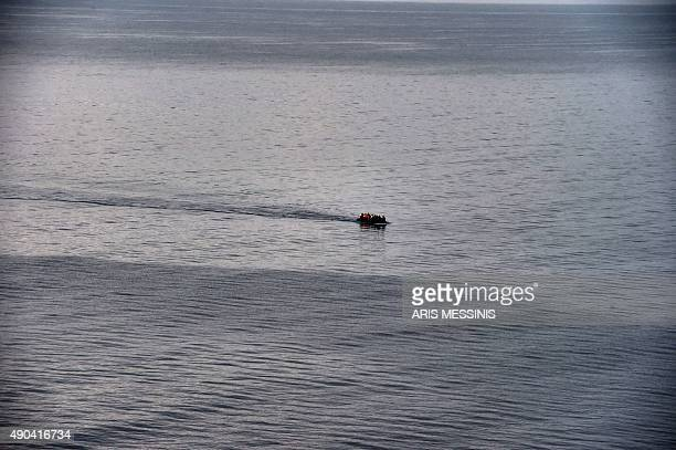 Refugees and migrants aboard an inflatable boat cross the Aegean Sea from Turkey to arrive to the Greek island of Lesbos on September 28 2015 UN...