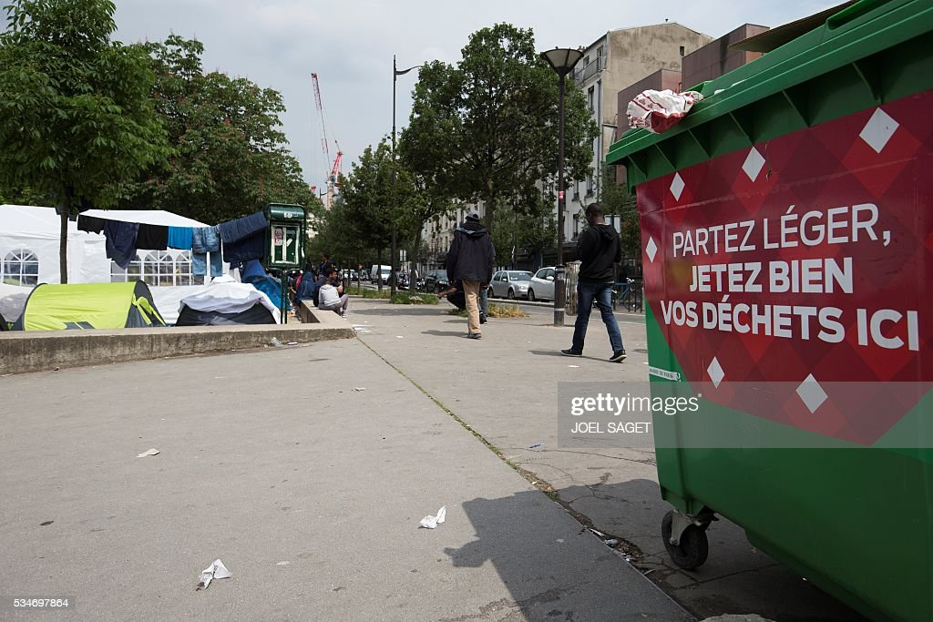 Refugees and migrants are pictured in a makeshift camp in Paris on May 27, 2016. SAGET