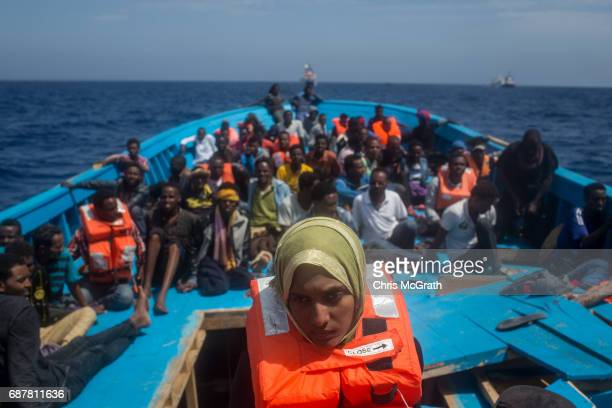 Refugees and migrants are seen on board a wooden boat as they wait for rescue crews from the Migrant Offshore Aid Station 'Phoenix' vessel on May 24...