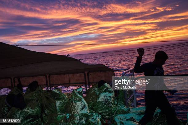 Refugees and migrants are seen on board the Migrant Offshore Aid Station Phoenix vessel after being rescued at sea on May 18 2017 in the Lampedusa...