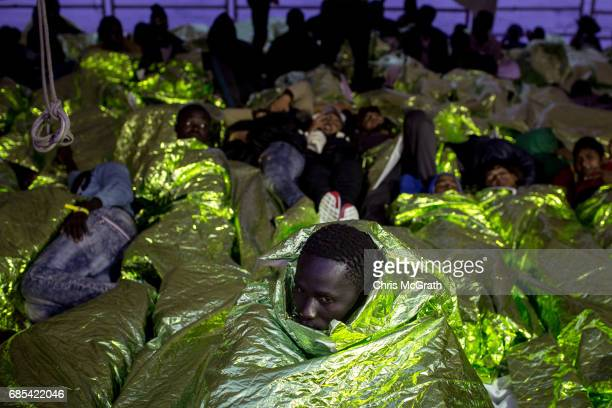 Refugees and migrants are seen on board the Migrant Offshore Aid Station 'Phoenix' vessel after being rescued at sea on May 19 2017 in Trapani Italy...