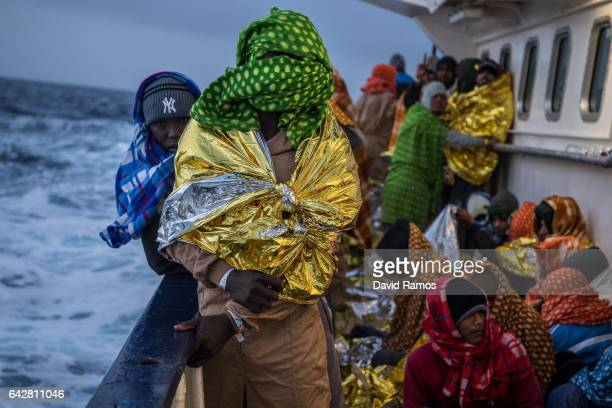 Refugees and migrants are seen on deck of the Spanish NGO Proactiva Open Arms rescue vessel Golfo Azzurro sailing towards the Italian port of...