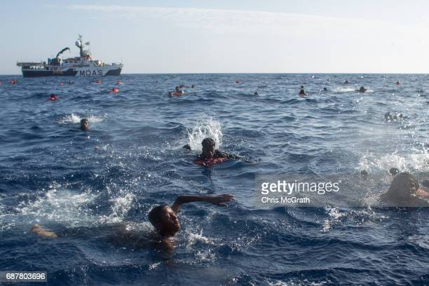 Refugees and migrants are seen swimming and yelling for assitance from crewmembers from the Migrant Offshore Aid Station 'Phoenix' vessel after a...