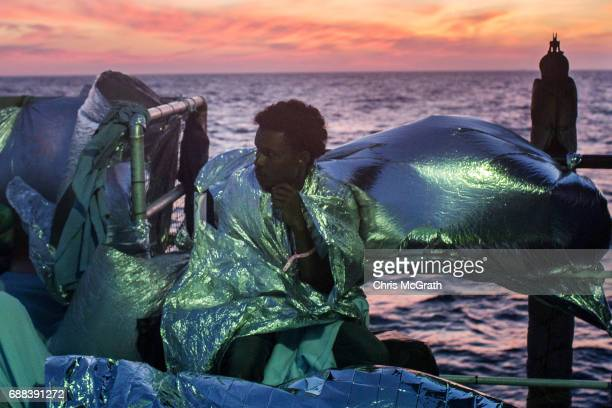 Refugees and migrants are seen wrapped in blankets on board the Migrant Offshore Aid Station 'Phoenix' vessel on May 25 2017 off Lampedusa Italy The...