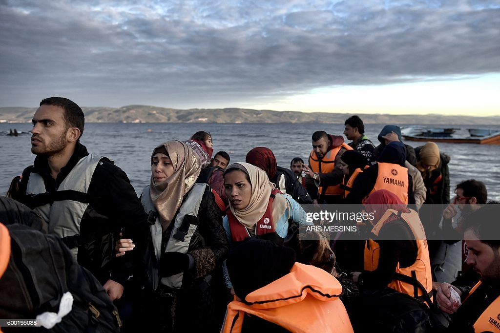 Refugees and migrants arrive at the Greek island of Lesbos after crossing the Aegean sea from Turkey on December 4 2015 / AFP / ARIS MESSINIS