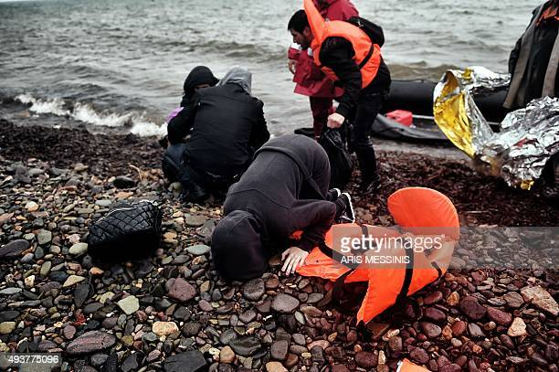 Refugees and migrants arrive on the Greek Lesbos island after crossing the Aegean Sea from Turkey on October 22 2015 An EU scheme to relocate asylum...
