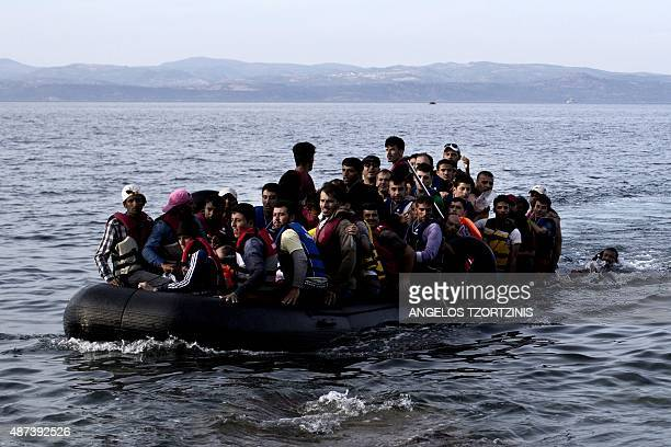 Refugees and migrants arrive on the shores of the Greek island of Lesbos after crossing the Aegean Sea from Turkey on an inflatable boat on September...