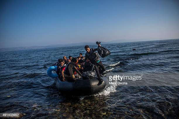 Refugees and migrants arrive on the shores of the Greek island of Lesbos after crossing the Aegean sea from Turkey on an inflatable boat on October 5...