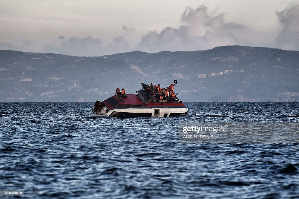 Refugees and migrants call for help as their boat is ready to sink off the Greek island of Lesbos island while crossing the Aegean sea from Turkey on...