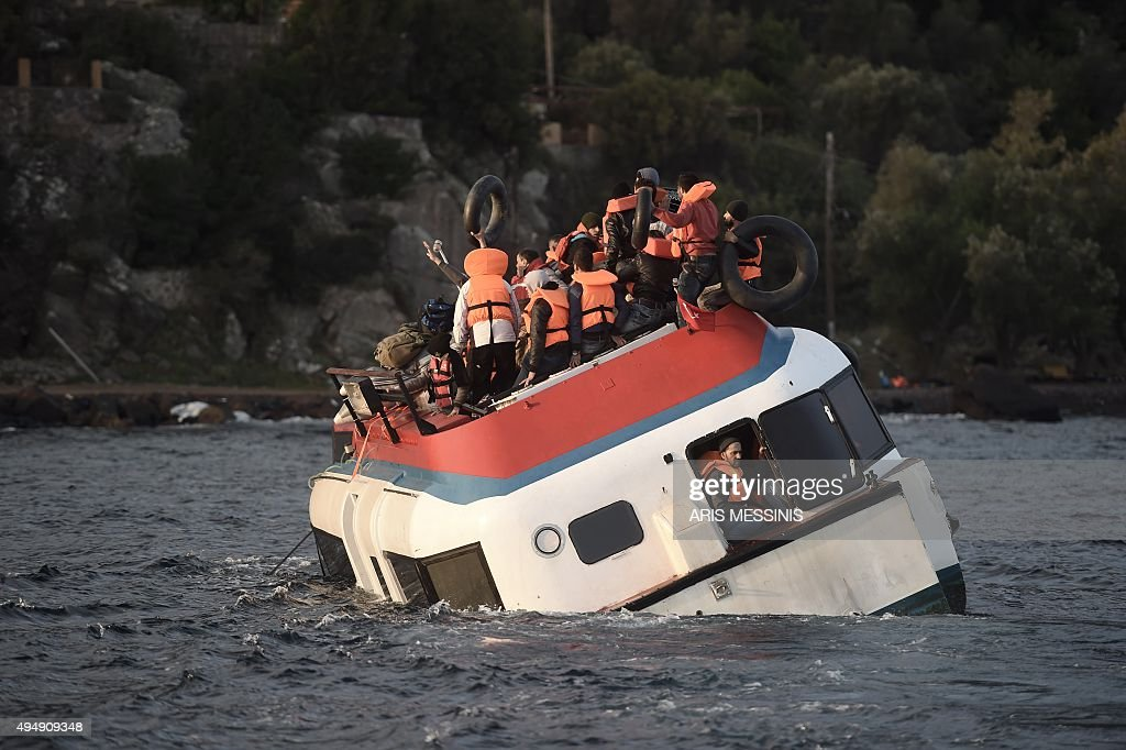 Refugees and migrants call for help as their boat sinks off the Greek island of Lesbos after crossing the Aegean sea from Turkey on October 30 2015...