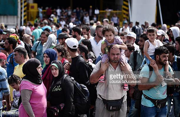 Refugees and migrants disembark from the Greek government chartered Eleftherios Venizelos ferry in the port of Piraeus on September 9 2015 Thousands...
