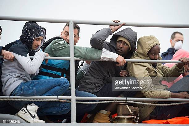 Refugees and migrants from Syrian Afghanistan and Eritrea sit on deck of a vessel of the Greek Coast guard after trying to cross the sea from Turkey...