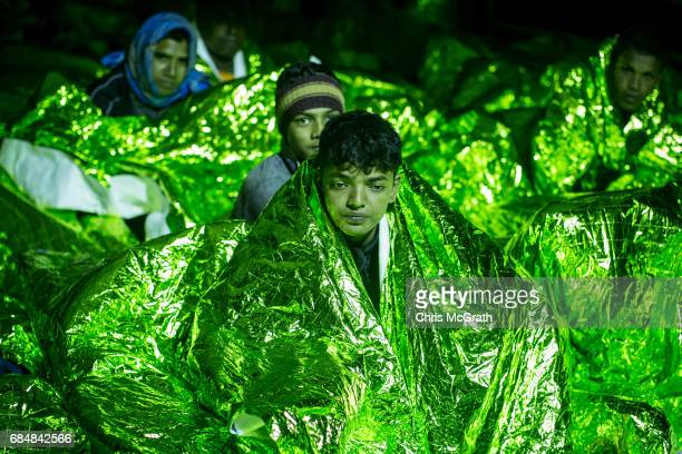 Refugees and migrants keep warm under blankets on board the Migrant Offshore Aid Station Phoenix vessel after being rescued at sea on May 18 2017 in...