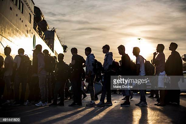 Refugees and migrants line up to board a ferry after arriving on the shores of the Greek island of Lesbos after crossing the Aegean sea from Turkey...