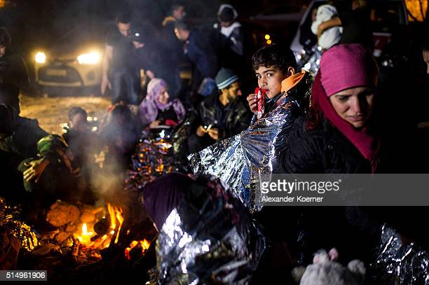 Refugees and migrants mainly from Afghanistan and Syria warm themselves after arriving on an inflatable boat with other refugees crossing the sea...