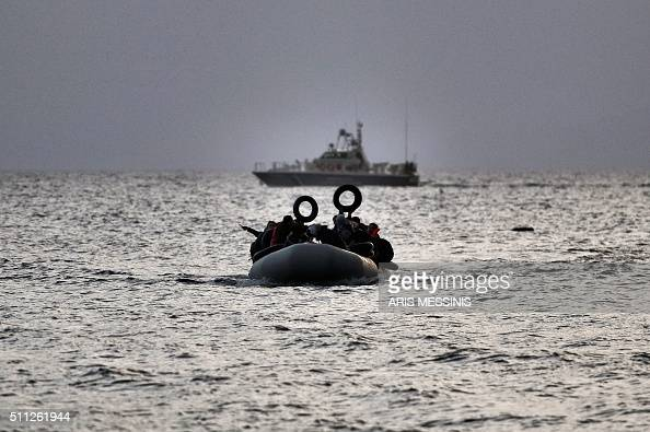 Refugees and migrants on a dinghy approach Mytilene on the northern island of Lesbos after crossing the Aegean sea from Turkey on February 19 2016...