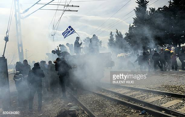 TOPSHOT Refugees and migrants protest as a unexploded gas canister explodes mistakenly near by as they rally demanding the reopening of the border...