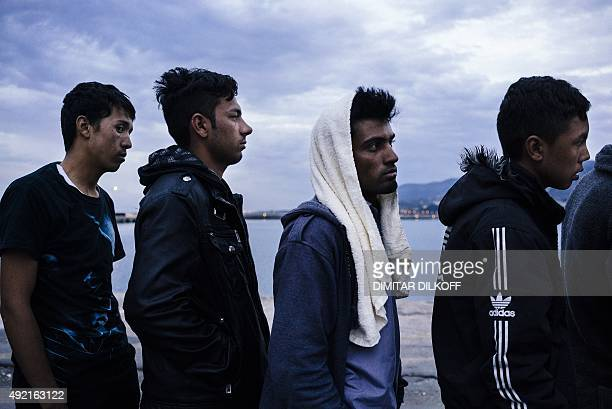 Refugees and migrants queue for food distribution at the port of Mytilene on the Greek island of Lesbos on October 10 2015 Greece was hit by a huge...
