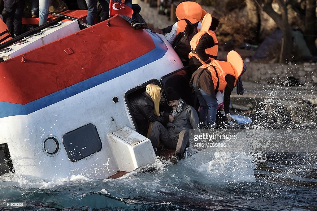 Refugees and migrants react as their boat sinks off the Greek island of Lesbos after crossing the Aegean sea from Turkey on October 30 2015 AFP PHOTO...