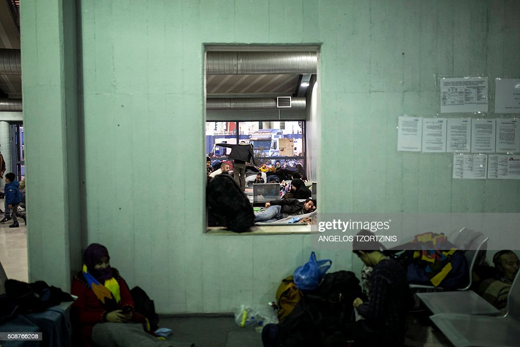 Refugees and migrants rest inside a passenger terminal at the port of Piraeus near Athens on February 6, 2016. More than a million migrants landed in the 28-nation European Union last year, most of them crossing into Greece from Turkey, and then making their way through the Balkans to Germany and other northern member states. / AFP / ANGELOS TZORTZINIS