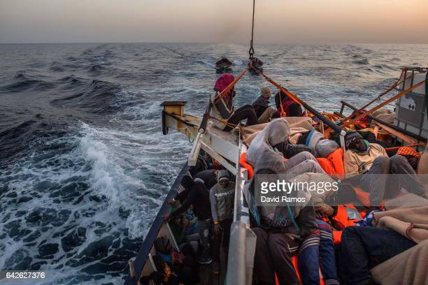 Refugees and migrants rest on the deck of the Spanish NGO Proactiva Open Arms rescue vessel Golfo Azzurro after being rescued off Libyan coast north...
