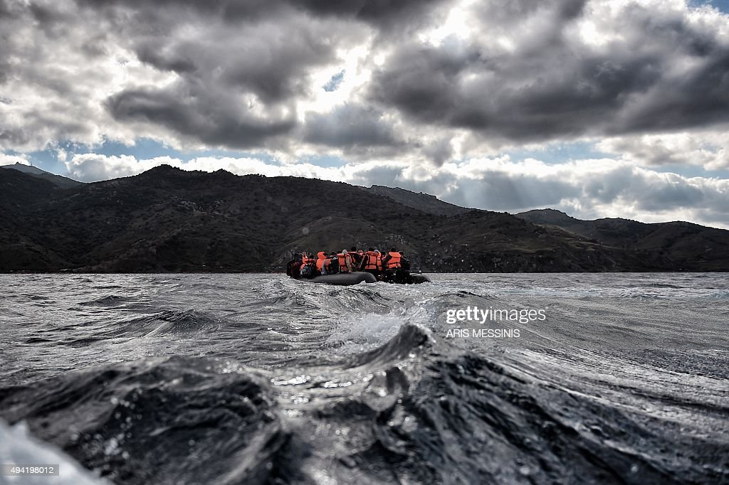 Refugees and migrants sail towards the Greek island of Lesbos on October 25 2015 as they cross the Aegean sea from Turkey At least three migrants two...