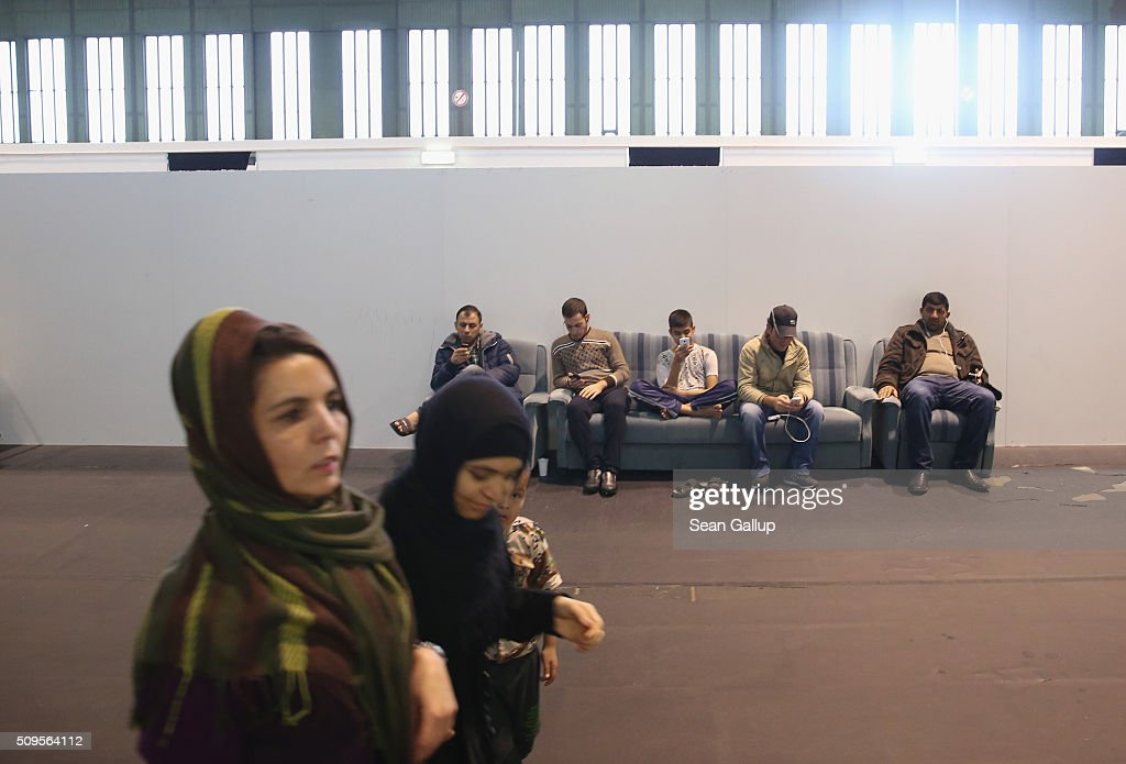 Refugees and migrants seeking asylum in Germany, including men with smartphones sitting on a couch, while away time in Hangar 7 where they live for now at former Tempelhof Airport on February 11, 2016 in Berlin, Germany. Tempelhof, once an airport in the city center and first built in the 1930s, now houses approximately 2,600 refugees in three former hangars. Berlin city authorities recently approved plans to expand its capacity to house the newcomers with an additional 90 shelters with space for 30,000 people. An estimated 50,000-80,000 migrants and refugees already live in Berlin. Germany received 1.1 million refugees and migrants in 2015 and is expecting to continue to receive large numbers in 2016.