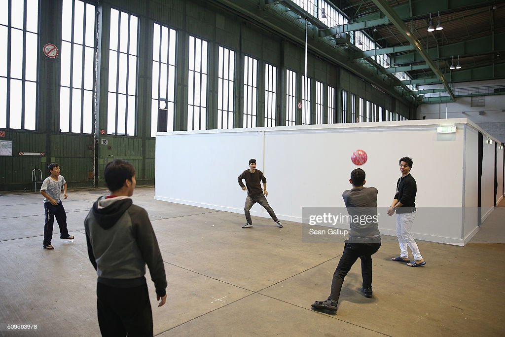 Refugees and migrants seeking asylum in Germany play volleyball in Hangar 7 at former Tempelhof Airport on February 11, 2016 in Berlin, Germany. Tempelhof, once an airport in the city center and first built in the 1930s, now houses approximately 2,600 refugees in three former hangars. Berlin city authorities recently approved plans to expand its capacity to house the newcomers with an additional 90 shelters with space for 30,000 people. An estimated 50,000-80,000 migrants and refugees already live in Berlin. Germany received 1.1 million refugees and migrants in 2015 and is expecting to continue to receive large numbers in 2016.