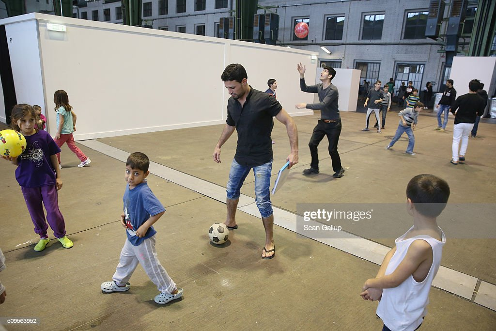 Refugees and migrants seeking asylum in Germany play with balls in Hangar 7 at former Tempelhof Airport on February 11, 2016 in Berlin, Germany. Tempelhof, once an airport in the city center and first built in the 1930s, now houses approximately 2,600 refugees in three former hangars. Berlin city authorities recently approved plans to expand its capacity to house the newcomers with an additional 90 shelters with space for 30,000 people. An estimated 50,000-80,000 migrants and refugees already live in Berlin. Germany received 1.1 million refugees and migrants in 2015 and is expecting to continue to receive large numbers in 2016.
