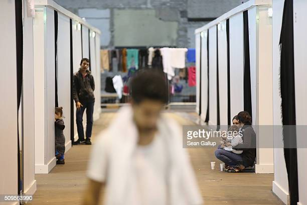 Refugees and migrants seeking asylum in Germany walk among cubicles that contain bund beds and offer at least some privacy in Hangar 7 at former...