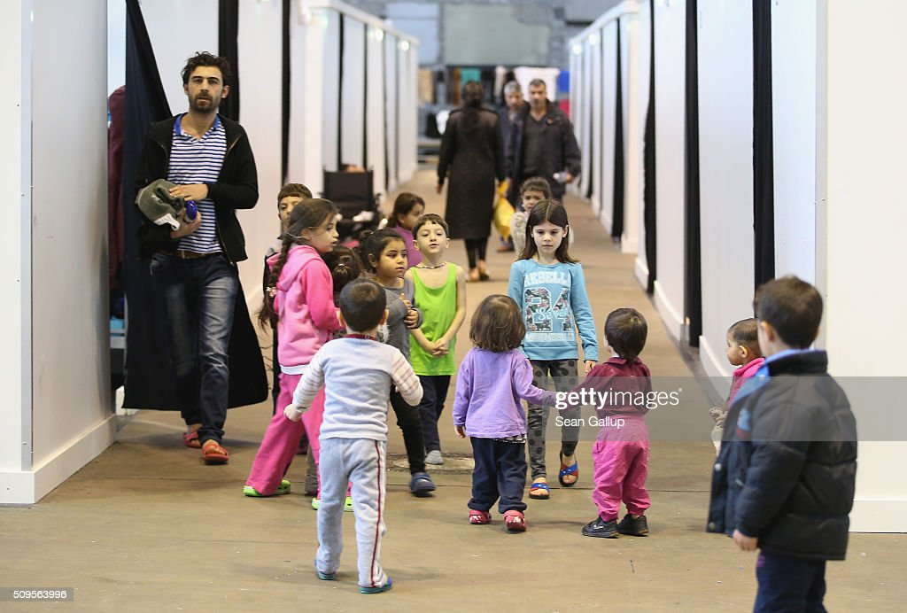 Refugees and migrants seeking asylum in Germany walk among cubicles that contain bund beds and offer at least some privacy in Hangar 7 at former Tempelhof Airport on February 11, 2016 in Berlin, Germany. Tempelhof, once an airport in the city center and first built in the 1930s, now houses approximately 2,600 refugees in three former hangars. Berlin city authorities recently approved plans to expand its capacity to house the newcomers with an additional 90 shelters with space for 30,000 people. An estimated 50,000-80,000 migrants and refugees already live in Berlin. Germany received 1.1 million refugees and migrants in 2015 and is expecting to continue to receive large numbers in 2016.