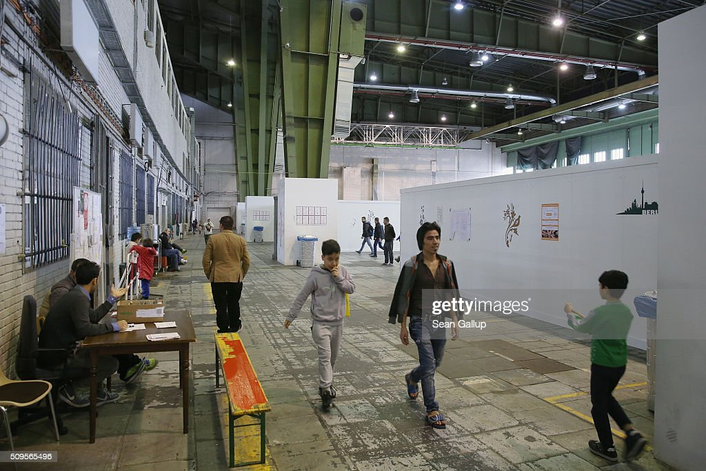 Refugees and migrants seeking asylum in Germany walk among cubicles that contain bund beds and offer at least some privacy in Hangar 2 at former Tempelhof Airport on February 11, 2016 in Berlin, Germany. Tempelhof, once an airport in the city center and first built in the 1930s, now houses approximately 2,600 refugees in three former hangars. Berlin city authorities recently approved plans to expand its capacity to house the newcomers with an additional 90 shelters with space for 30,000 people. An estimated 50,000-80,000 migrants and refugees already live in Berlin. Germany received 1.1 million refugees and migrants in 2015 and is expecting to continue to receive large numbers in 2016.