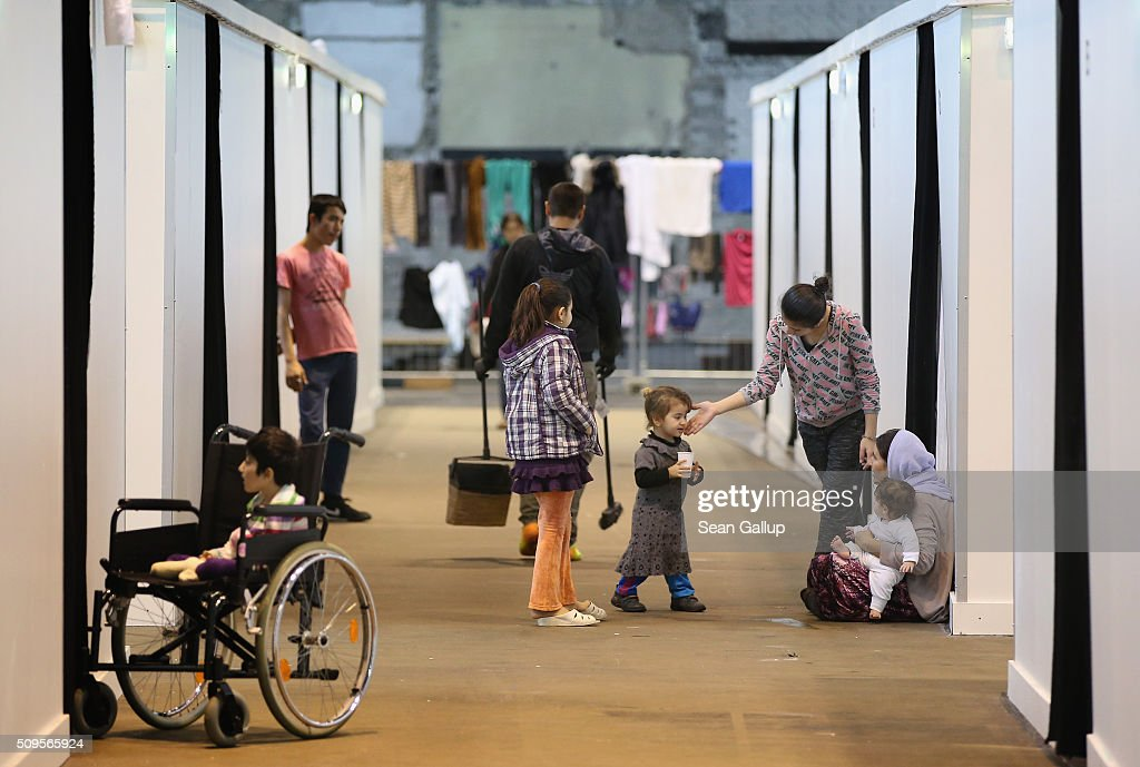 Refugees and migrants seeking asylum in Germany walk among cubicles that contain bunk beds and offer at least some privacy in Hangar 7 at former Tempelhof Airport on February 11, 2016 in Berlin, Germany. Tempelhof, once an airport in the city center and first built in the 1930s, now houses approximately 2,600 refugees in three former hangars. Berlin city authorities recently approved plans to expand its capacity to house the newcomers with an additional 90 shelters with space for 30,000 people. An estimated 50,000-80,000 migrants and refugees already live in Berlin. Germany received 1.1 million refugees and migrants in 2015 and is expecting to continue to receive large numbers in 2016.