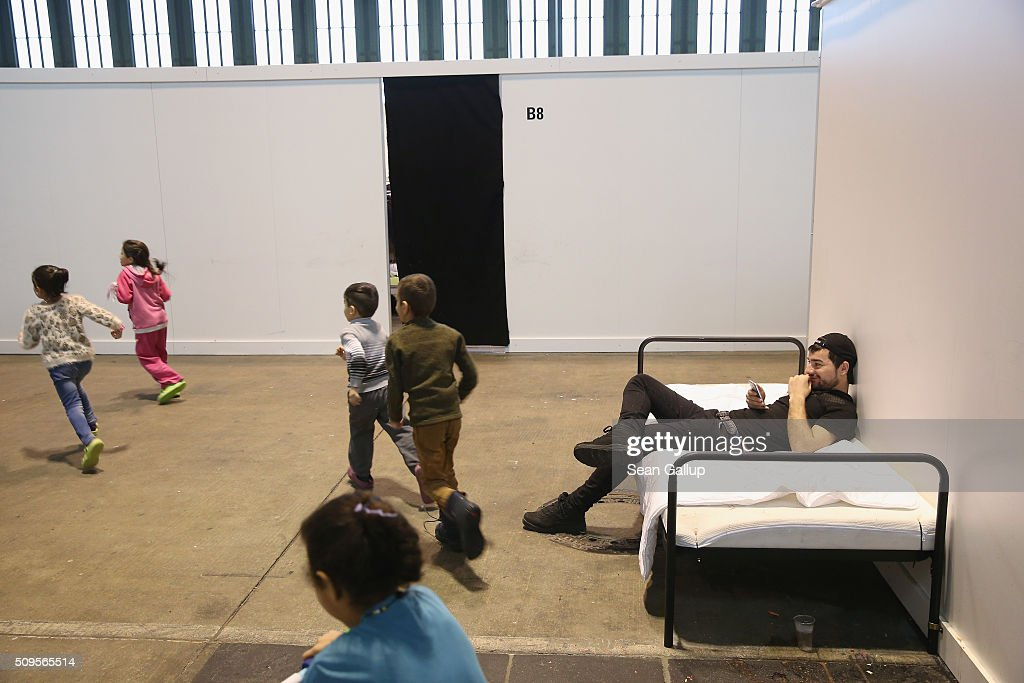 Refugees and migrants seeking asylum in Germany while away time among cubicles that contain bunk beds and offer at least some privacy in Hangar 7 at former Tempelhof Airport on February 11, 2016 in Berlin, Germany. Tempelhof, once an airport in the city center and first built in the 1930s, now houses approximately 2,600 refugees in three former hangars. Berlin city authorities recently approved plans to expand its capacity to house the newcomers with an additional 90 shelters with space for 30,000 people. An estimated 50,000-80,000 migrants and refugees already live in Berlin. Germany received 1.1 million refugees and migrants in 2015 and is expecting to continue to receive large numbers in 2016.