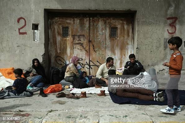 Refugees and migrants sit on the ground outside a warehouse at the port of Piraeus southwest of central Athens on February 29 2016 More than 2000...