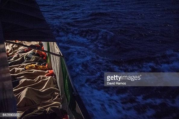 Refugees and migrants sleep wrapped in blankets on deck of the Spanish NGO Proactiva Open Arms rescue vessel Golfo Azzurro after being rescued by the...