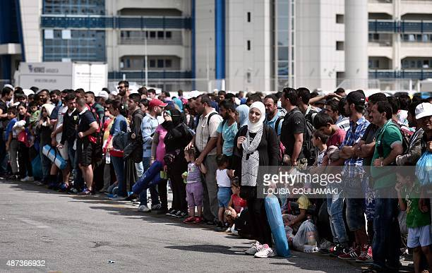 Refugees and migrants wait for buses after disembarking from the Greek government chartered Eleftherios Venizelos ferry in the port of Piraeus on...