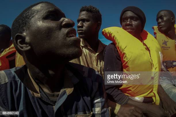 Refugees and migrants wait in a rescue boat before being transfered to the Migrant Offshore Aid Station Phoenix vessel after being rescued at sea on...