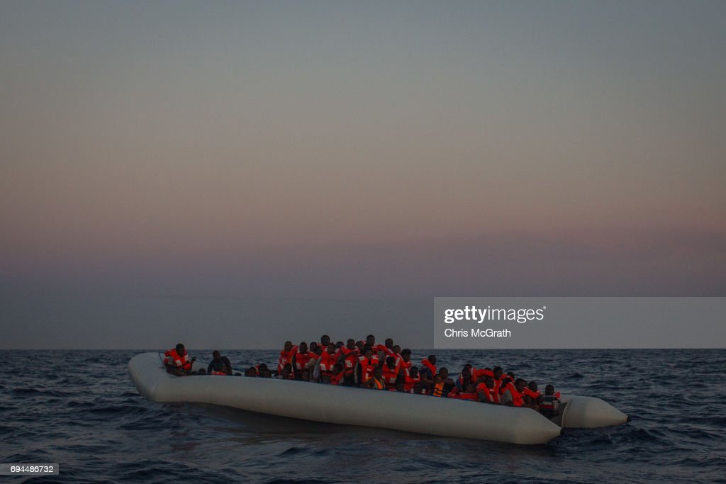 Refugees and migrants wait in a small rubber boat to be rescued by crewmembers from the Migrant Offshore Aid Station (MOAS) Phoenix vessel on June 10, 2017 off Lampedusa, Italy. An estimated 230,000 refugees and migrants will arrive in Italy this year as numbers of refugees and migrants attempting the dangerous central mediterranean crossing from Libya to Italy continues to rise since the same time last year. So far this year more than 58,000 people have arrived in Italy and 1,569 people have died attempting the crossing. Libya continues to be the primary departure point for refugees and migrants taking the central mediterranean route to Sicily. In an attempt to slow the flow of migrants, Italy recently signed a deal with Libya, Chad and Niger outlining a plan to increase border controls and add new reception centers in the African nations, which are key transit points for migrants heading to Italy. MOAS is a Malta based NGO dedicated to providing professional search-and-rescue assistance to refugees and migrants in distress at sea. Since the start of the year MOAS have rescued and assisted more than 4000 people and are currently patrolling and running rescue operations in international waters off the coast of Libya.
