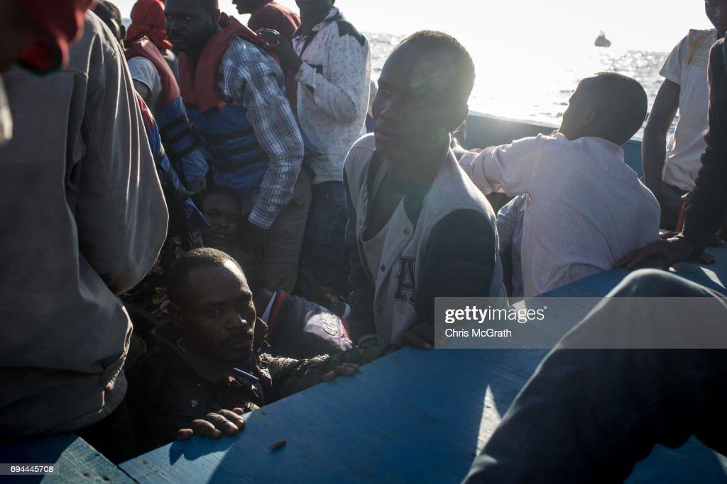 Refugees and migrants wait in a small wooden boat to be rescued by crewmembers from the Migrant Offshore Aid Station (MOAS) Phoenix vessel on June 10, 2017 off Lampedusa, Italy. An estimated 230,000 refugees and migrants will arrive in Italy this year as numbers of refugees and migrants attempting the dangerous central Mediterranean crossing from Libya to Italy continues to rise since the same time last year. So far this year more than 58,000 people have arrived in Italy and 1,569 people have died attempting the crossing. Libya continues to be the primary departure point for refugees and migrants taking the central Mediterranean route to Sicily. In an attempt to slow the flow of migrants, Italy recently signed a deal with Libya, Chad and Niger outlining a plan to increase border controls and add new reception centers in the African nations, which are key transit points for migrants heading to Italy. MOAS is a Malta based NGO dedicated to providing professional search-and-rescue assistance to refugees and migrants in distress at sea. Since the start of the year MOAS have rescued and assisted more than 4000 people and are currently patrolling and running rescue operations in international waters off the coast of Libya.