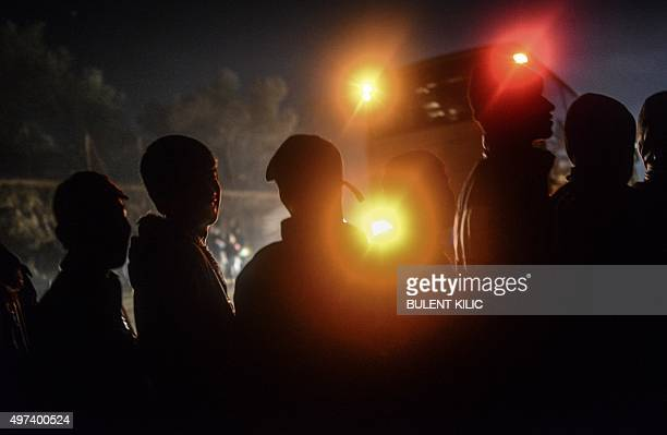 Refugees and migrants wait in line for food in a camp on the Greek island of Lesbos after crossing the Aegean Sea from Turkey on November 16 2015...