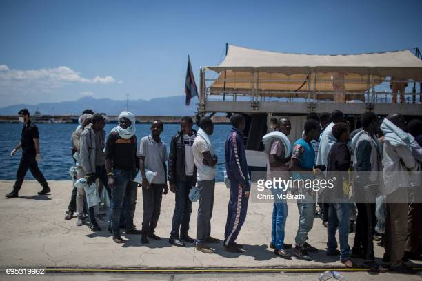 Refugees and migrants wait to be processed after disembarking the Migrant Offshore Aid Station Phoenix vessel at port on June 12 2017 in Reggio...