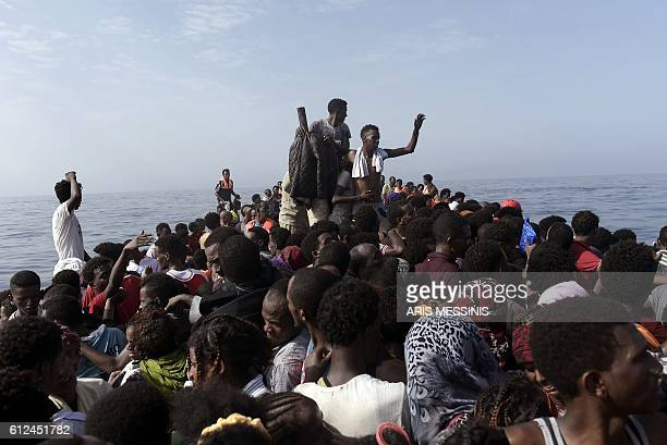 Refugees and migrants wait to be rescued by members of Proactiva Open Arms NGO in the Mediterranean Sea some 12 nautical miles north of Libya on...