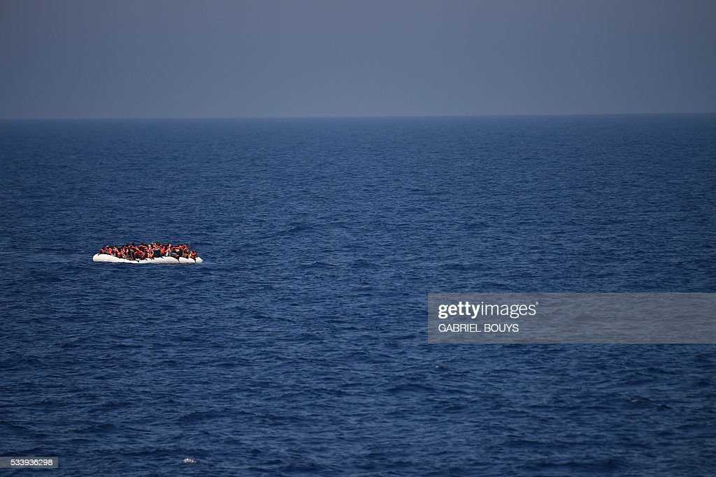 Refugees and migrants wait to be rescued during an operation at sea with the Aquarius, a former North Atlantic fisheries protection ship now used by humanitarians SOS Mediterranee and Medecins Sans Frontieres (Doctors without Borders), on May 24, 2016 in the Mediterranean sea in front of the Libyan coast. / AFP / GABRIEL