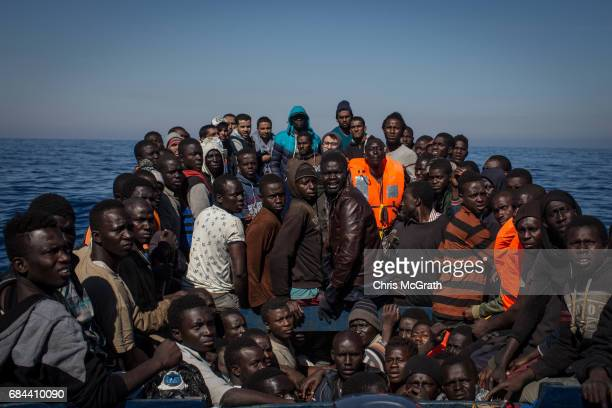 Refugees and migrants wait to be rescued from a small wooden boat by crew members from the Migrant Offshore Aid Station Phoenix vessel on May 18 2017...